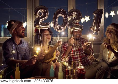 Cheerful couples making festive atmosphere at New Year eve home party. New Year, home party, friends time together