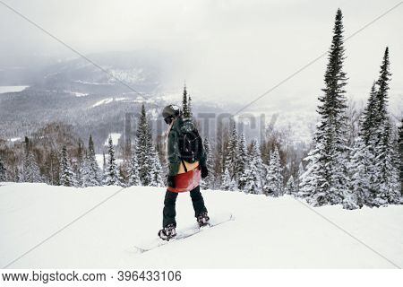 Woman snowboarder freerider on a snowy slope in mountains.