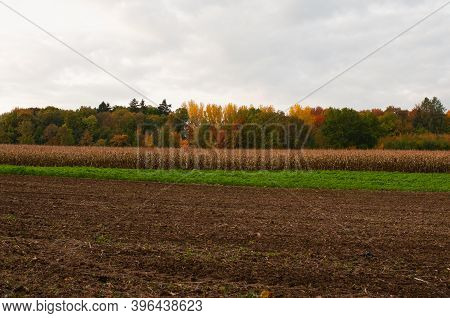 Gray Cloudy Sky Over Rural Landscape In Autumn With Agricultural Fields And Colorful Forest