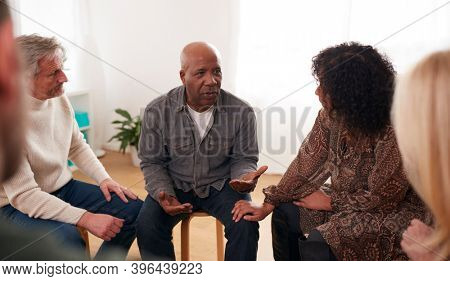 Man Speaking At Support Group Meeting For Mental Health Or Dependency Issues In Community Space