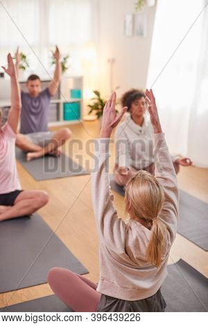 Group With Teacher Sitting On Exercise Mats Stretching In Yoga Class Inside Community Center