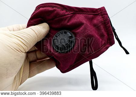 Doctor Hand In Rubber Medical Glove Holding A Red Medical Protective Mask.