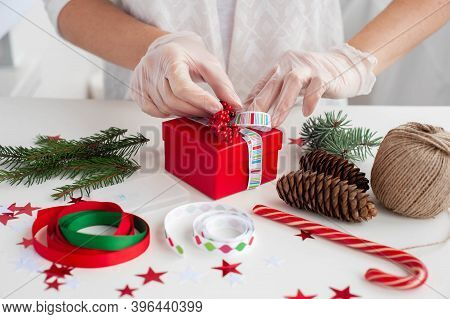 Packing A Christmas Present During The Coronavirus Epidemic. A Woman In Medical Gloves Decorates The