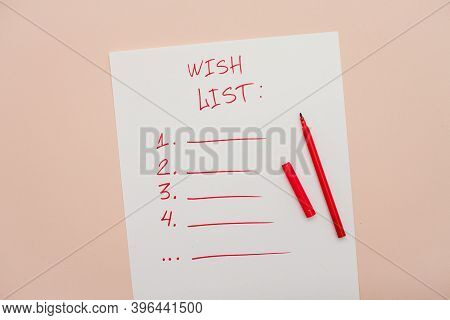 Inscription In Red Felt-tip Pen Wish List On A White Blank Sheet Of Paper. New Years Wish List. Lett