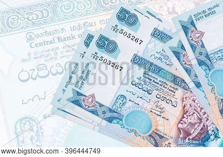 50 Sri Lankan Rupees Bills Lies In Stack On Background Of Big Semi-transparent Banknote. Abstract Pr