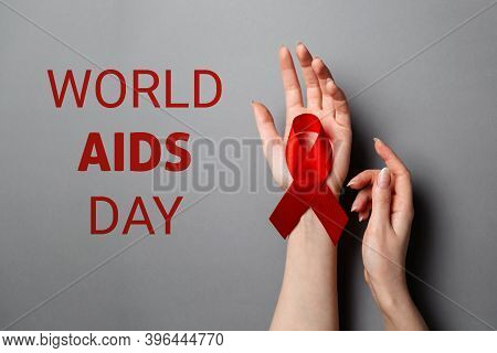 Females Hands, On The Palm Is A Red Ribbon, A Symbol Of The Fight Against Aids. Text. Gray Backgroun