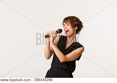Carefree Attractive Girl Singing In Microphone, Performing, Have Fun At Karaoke, Standing Over White