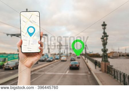 A Females Hand Holds A Smartphone With An Online Map App. In The Background Is A Road With Car And G