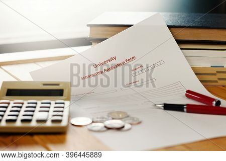 School Scholarship Application Form On Wooden Table With Books, Coins, Calculator
