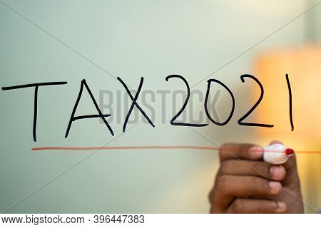 Hands Marking Line On Tax 2021 Test Written On Glass - Concept Of New Year 2021 Tax Pay And Return C