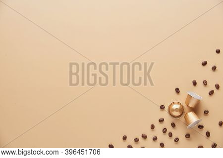 Caffeine, Hot Drinks And Objects Concept - Close Up Of Golden Capsules Or Pods For Coffee Mashine Wi