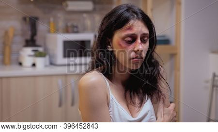 Beaten Woman Siting On The Chair Pushed By Violent Husband. Traumatised Abused Terrified Beaten Wife