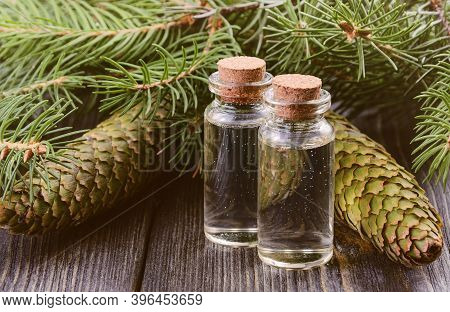 Two Bottles Of Spruce Essential Oil And Spruce Cones With Fir Branches On Dark Wooden Table. The Con