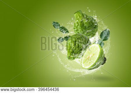 Water Splashing On Bergamot Fruit With Leaf Isolated On Green Background.