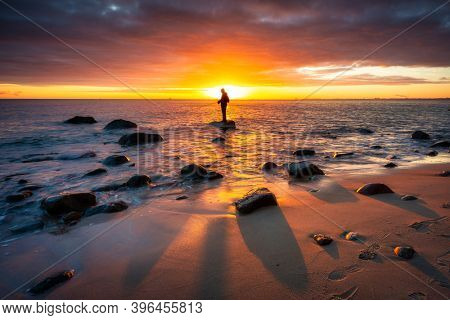 Angler standing on the rock in Baltic Sea at sunrise, Gdynia. Poland