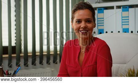 Hispanic Woman Typing On Computer And Looking At Camera Smiling. Entrepreneur Working In Modern Prof