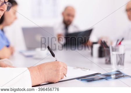 Close Up Of Unknown Doctor Taking Notes On Clipboard During Medical Briefing In Conference Room. Cli