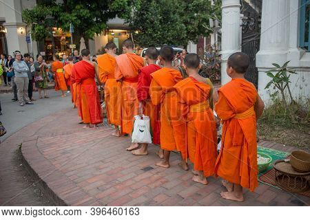 Luang Prabang, Laos : March-02-2019 : Buddhist Monks In A Rows With Alms Bowl Walking On The Street