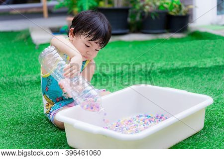 Preschool Child Boy Is Using Two Hands To Hold Plastic Bottle To Pour Water Beads Or Rainbow Beads I