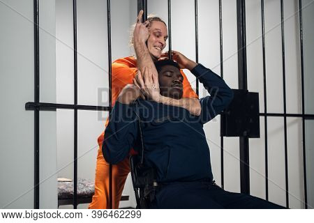 A Crazy Prison Inmate Strangles A Black Warden Through The Bars Of A Maximum Security Prison. The Co
