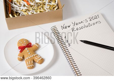 Phrase New Year's Resolutions 2021 In The Notebook And Pen. Gingerbread Man On Table.