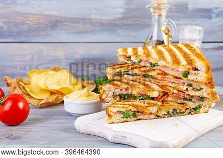 Club Sandwich With Ham, Cheese, Tomato, Salad And Chips