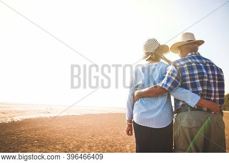 An Elderly Asian Couple Standing Hugging Each Other At The Beach, Seeing The Evening Light.