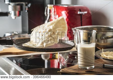 Person Is Flipping The Pancake Over By Throwing It. Concept Of Making Homemade Pancakes In Your Own