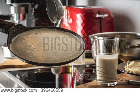 Person Pouring The Dough Into A Hot Pan And Frying Homemade Pancakes. Concept Of Making Pancakes In