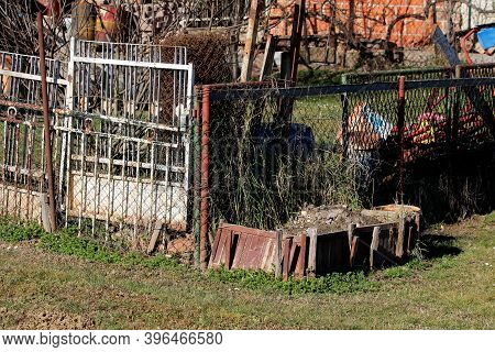 Cluttered Old Family House Backyard Filled With Construction Material Mixed With Tree Branches And O