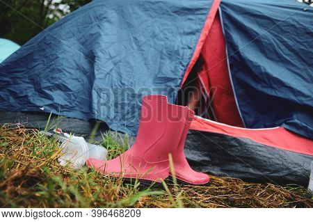 Details With Pink Rubber Boots Outside A Tent In A Camping Area Of A Music Festival During A Rainy S