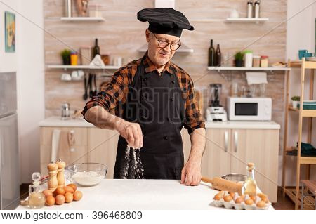 Chef Wearing Bonete And Apron While Preparing Ingredient For Delicious Recipe In Home Kitchen. Cook