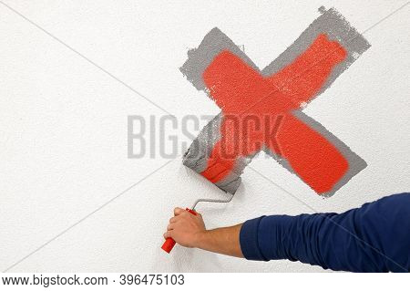 Worker Drew A Cross With A Roller On The White Wall