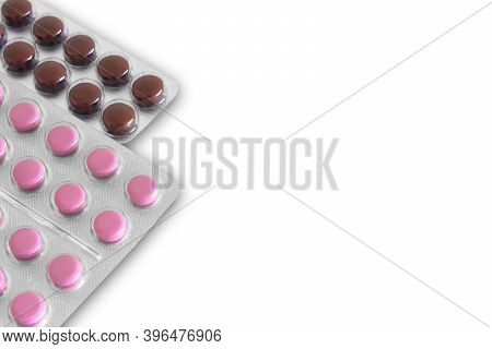 Brown And Pink Tablets In A Package On A White Background