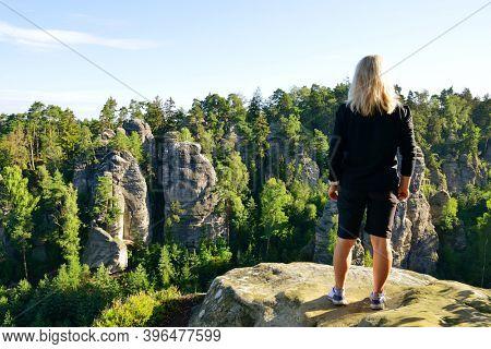 Woman looking at the sandstone rock in Prachovske skaly, Bohemian Paradise (Cesky Raj), Czechia.