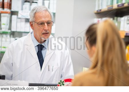 Senior pharmacist serving a female customer in his pharmacy