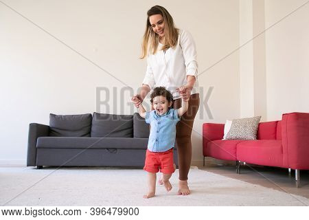Happy Mother Holding Son Hands And Teaching Him To Walk. Cheerful Curly Mixed-race Little Boy Walkin