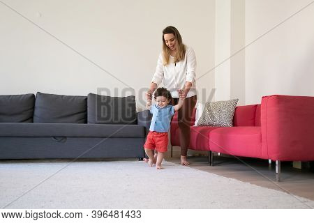 Loving Mother Holding Son Hands And Helping Him To Walk. Funny Curly Mixed-race Little Boy Learning