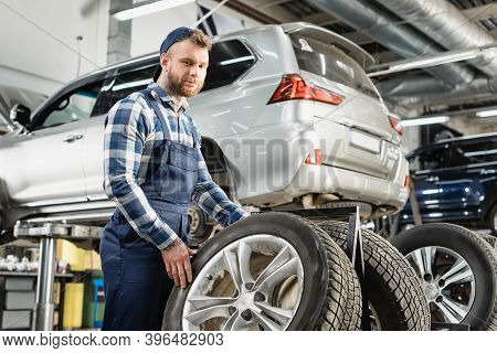 Mechanic Looking At Camera Near Wheel And Auto Raised On Car Lift