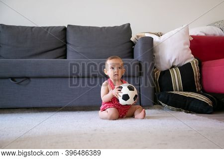 Thoughtful Baby Girl Holding Soccer Ball, Sitting On Carpet Barefoot And Looking Away. Lovely Toddle