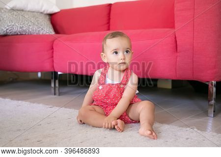 Adorable Little Baby Sitting On Carpet Barefoot In Living Room. Funny Pensive Girl In Red Dungarees
