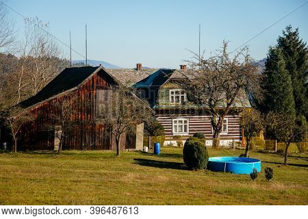 Small Brown House, Old Wooden Timber Hut With A Fence, Cottage Surrounded By Trees, Bohemian Paradis
