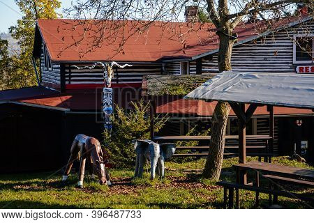 Small Brown House, Old Wooden Timber Hut With A Fence, Carved Statues Elephant, Horse, Indian Totem,