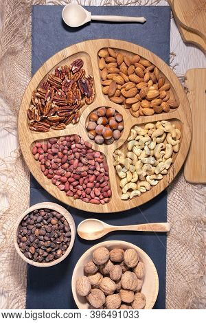 Selection Of Nuts Peanuts, Hazelnuts, Almonds, Cashews, Walnuts, Pecans On A Wooden Table. Top View