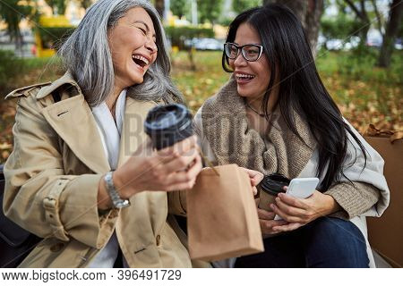 Cheerful Female Friends Chatting And Laughing On The Street