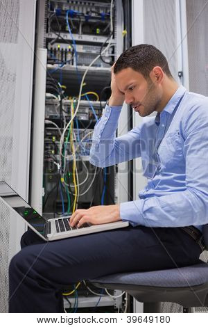 Data technician getting stressed over servers with laptop poster