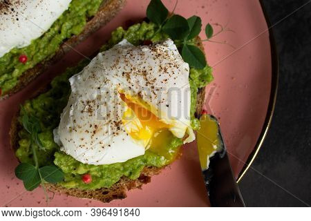 Top View: Cutted Poached Egg With Liquid Yolk On Fresh Avocado Cream On The Pink Plate. Egg Yolk On