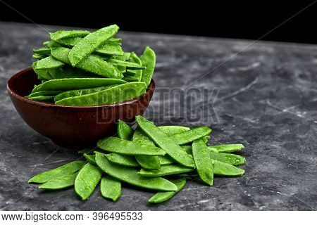 Sweet Green Peas In A Wooden Bowl On A Stone Background. Background With Sweet Green Pea Pods. Green