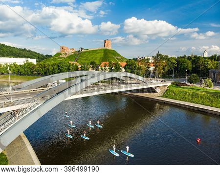 Stand Up Paddle Boarders Passing By Gediminas Tower, The Remaining Part Of The Upper Castle In Vilni