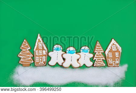 Group Of Ginger Snowmen In Protective Masks Among Gingerbread Houses And Fir Trees On A Green Backgr